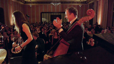 Bassist klatscht vor Publikum, Sängerin spielt Perkussion