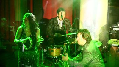 Schlagzeuger, Saxophonist und Sängerin auf der Bühne