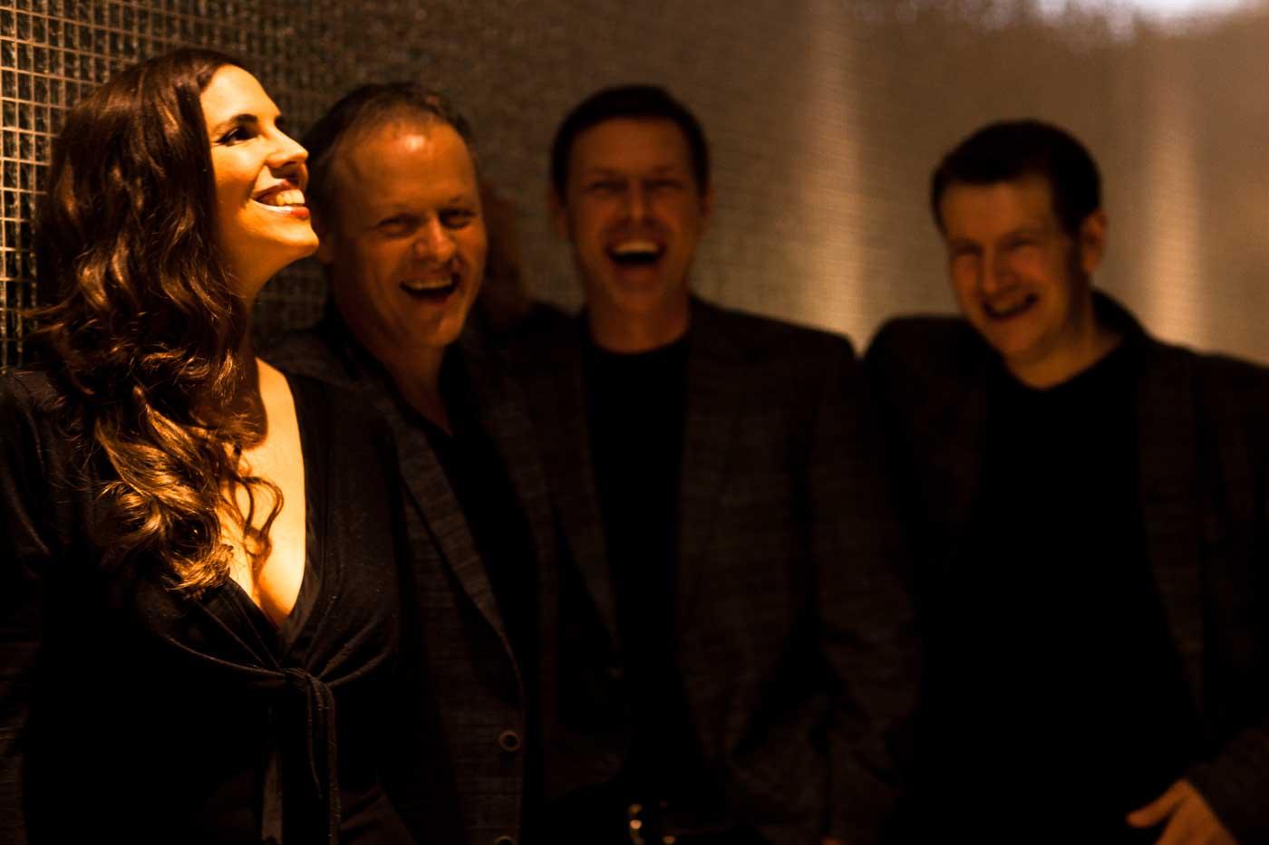 Drei Männer und eine Frau, lachend im Halbportrait