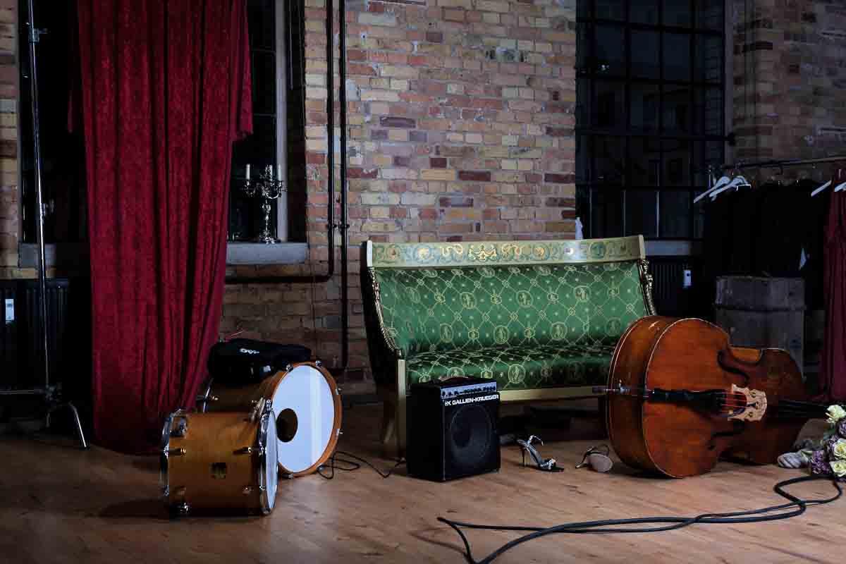 Instrumente, Sofa, Verstärker und Kabel vor rotem Vorhang