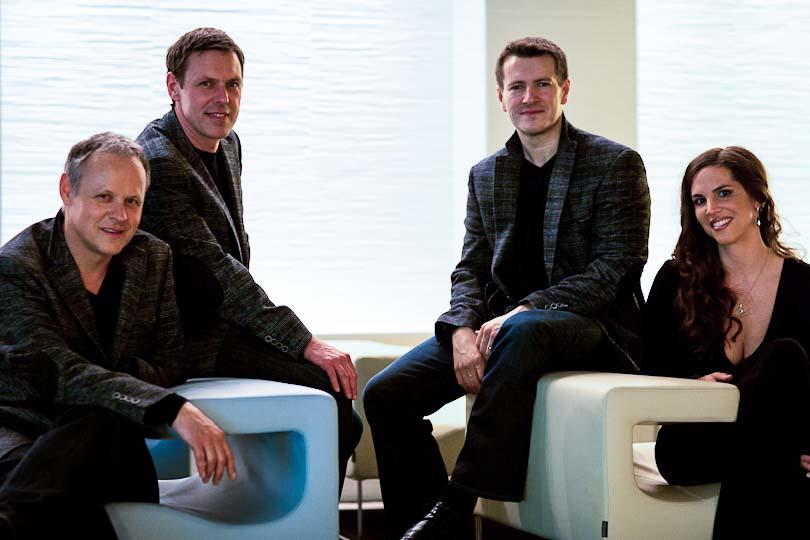 drei Männer und eine Frau sitzen auf Loungemöbeln