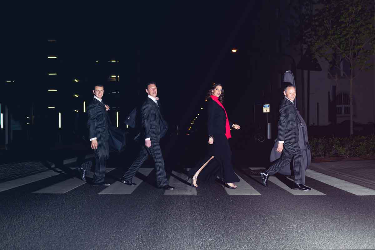 Quartett mit Instrumenten überquert Zebrasteifen