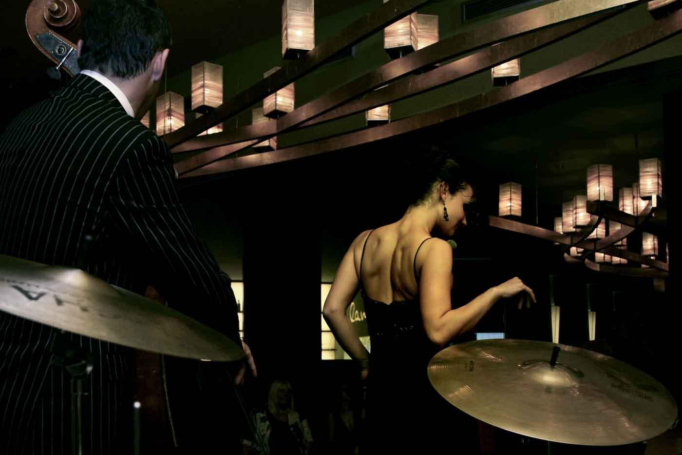 Bassspieler und Sängerin aus der Schlagzeug-Perspektive