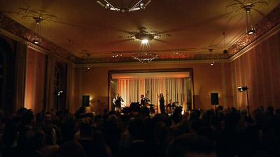 Publikum im Konzertsaal mit Bühne im Hintergrund
